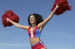 Smiling woman jumping in the air with outstretched pom-poms